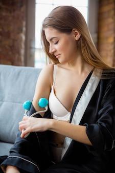 Donna che indossa un abito di seta che fa la sua routine quotidiana di cura della pelle a casa.