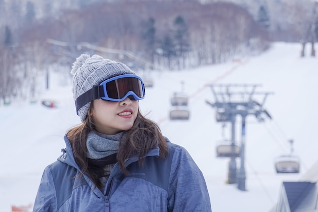 Лыжная одежда и очки женщины нося в горе зимы снега.