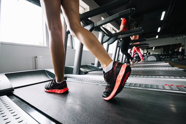 Woman wearing sneakers and using treadmill