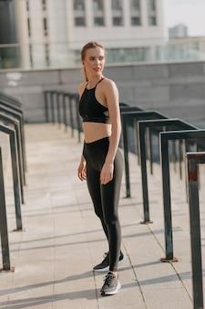 Donna che indossa abiti sportivi che si preparano per l'esercizio all'aperto.