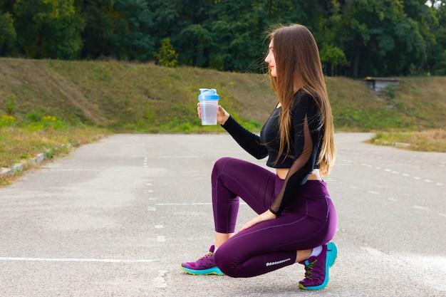Женщина носить спортивную одежду берет перерыв, чтобы пить воду.