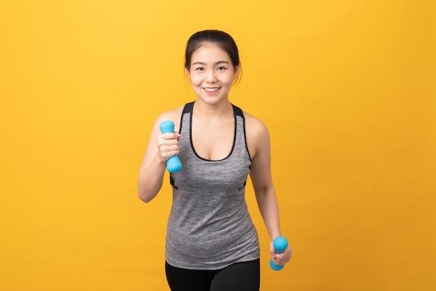 Женщина носит спортивную одежду и держит гантели