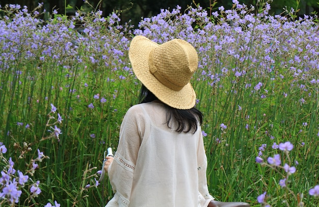 Woman wearing straw hat with her bicycle looking at beautiful pastel purple flower field