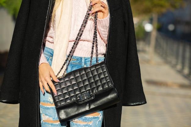 黒革のバッグを保持しているスタイリッシュなコート、ジーンズ、セーターを着ている女性。テキスト用のスペース