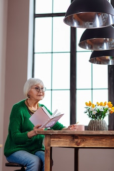 열린 성경 책을 들고 세련된 녹색 카디건과 안경을 착용하는 여자