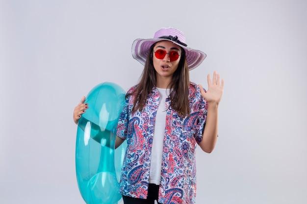 Женщина в летней шляпе и красных солнцезащитных очках держит надувное кольцо, стоя с открытой рукой, делает знак остановки, выглядит смущенным и удивленным на белом