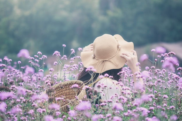 Woman wearing sun hat and bamboo basket visiting verbena flower field