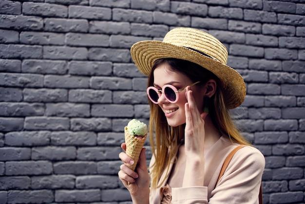サングラスと帽子をかぶった女性クロップドビューアーバンスタイルのレンガの壁