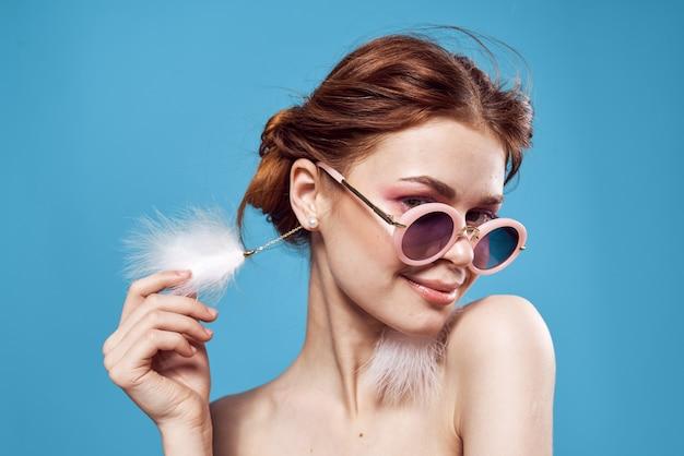 サングラスのイヤリングを身に着けている女性の贅沢な感情のクローズアップ青い背景。高品質の写真