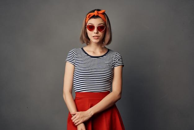 オレンジ色のヘッドバンドの贅沢なポーズのサングラスファッションを身に着けている女性