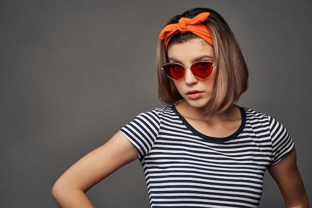 頭に包帯を巻いてファッションをポーズするストライプのtシャツにサングラスをかけている女性