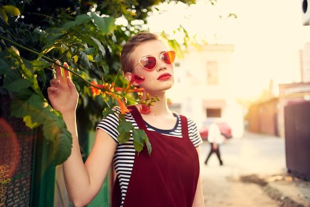 サングラスをかけている女性屋外の花の装飾夏