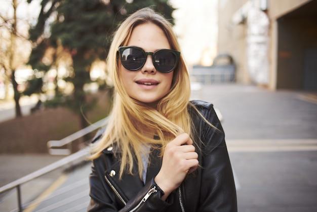 建物の散歩ファッションの魅力の近くで屋外でサングラスをかけている女性