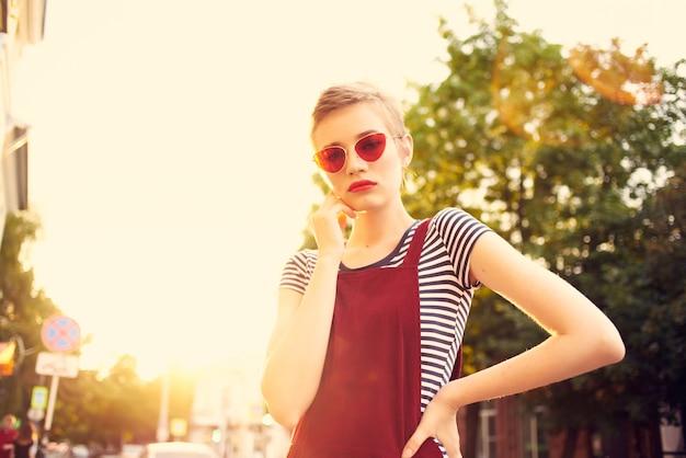 Женщина в солнцезащитных очках на открытом воздухе летние городские каникулы