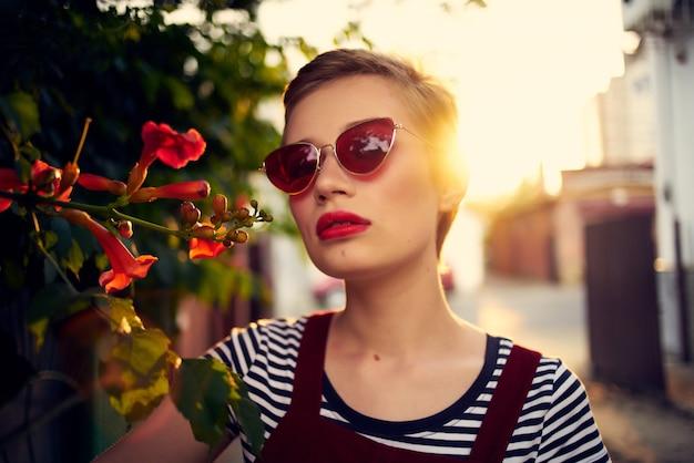 야외에서 선글라스를 끼고 패션 포즈를 취하는 여자