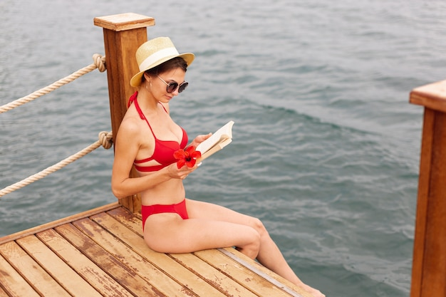 Woman wearing sunglasses and reading book on dock