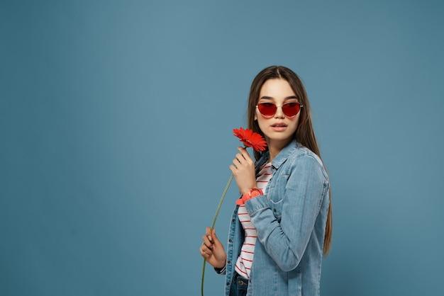 Женщина в солнцезащитных очках с красным цветком возле лица позирует моды крупным планом