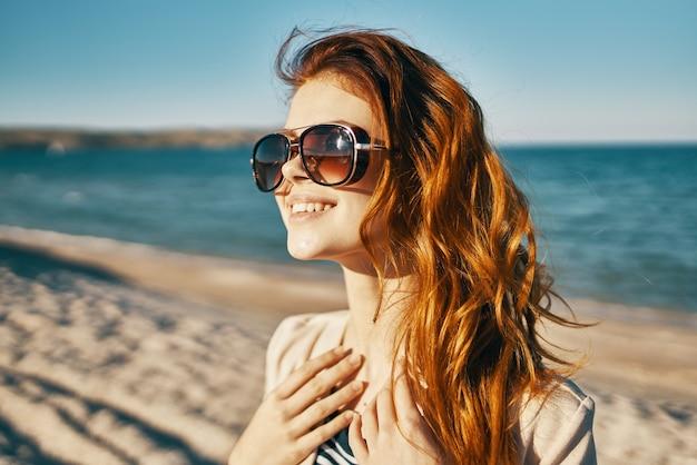 Женщина в солнцезащитных очках скал пейзаж море. фото высокого качества