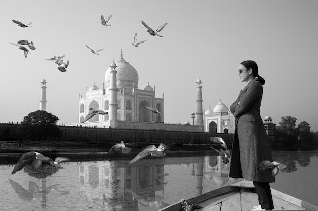 Woman wearing sunglasses standing on a boat with taj mahal in background.