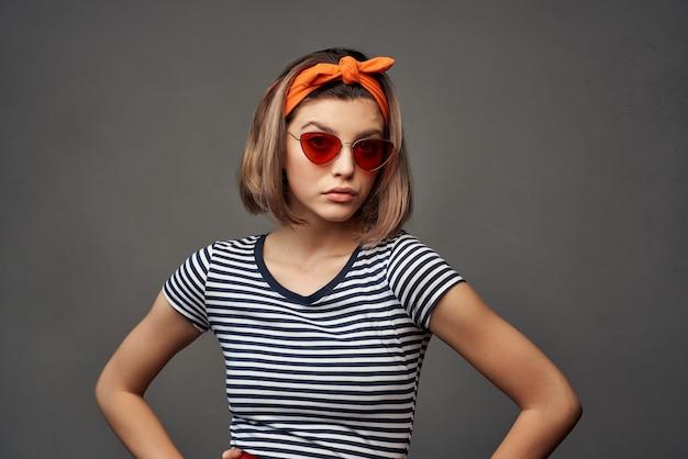 頭の孤立した背景のファッションにオレンジ色の包帯でサングラスをかけている女性