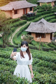 Woman wearing surgical face mask and using mobile smartphone in beautiful tea garden