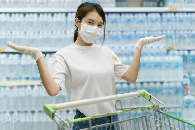 Женщина нося хирургические маску и перчатки, покупая питьевую воду в супермаркете. паника по магазинам после пандемии коронавируса.