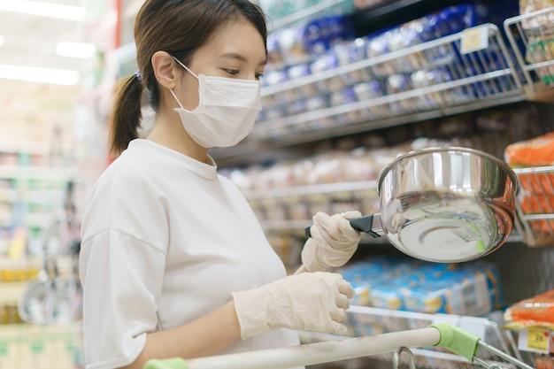 Женщина носить хирургические маски и перчатки, покупая горшок из нержавеющей стали в супермаркете. паника по магазинам после пандемии коронавируса.