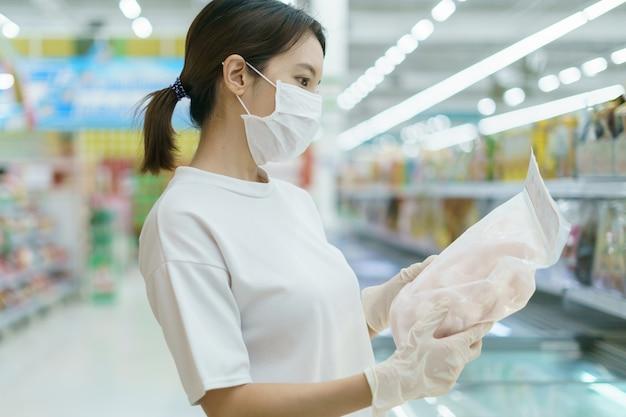 Женщина нося хирургические маску и перчатки, выбирая замороженную рыбу в супермаркете после пандемии коронавируса.