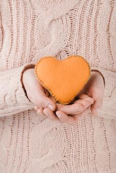 Woman wearing sweater holding orange heart