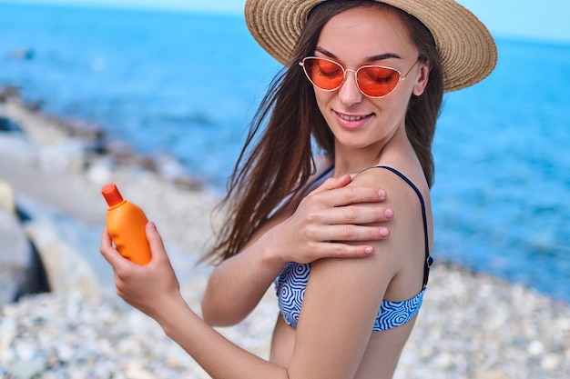 Woman wearing swimsuit, straw hat and bright red sunglasses apply sunscreen on her shoulder during sunbathing and relaxing by the sea in summertime