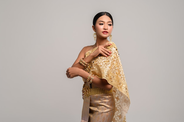 Woman wearing thai clothes and right hand grasping her shoulders.