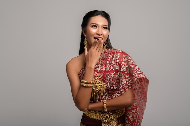 Woman wearing thai dress that made a hand symbol