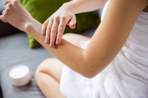 Donna che indossa un asciugamano facendo la sua routine quotidiana di cura della pelle a casa.