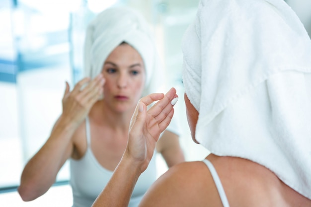 Woman wearing a towel on her hair is applying face cream in the mirror