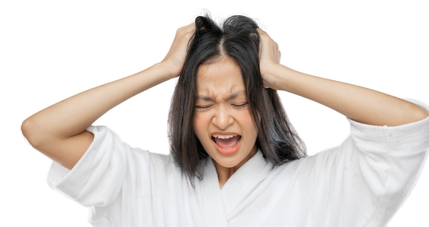 A woman wearing a towel holds her head and screams with a frustrated expression