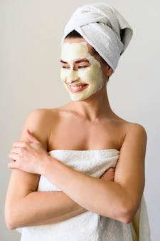 Woman wearing a towel with face mask on
