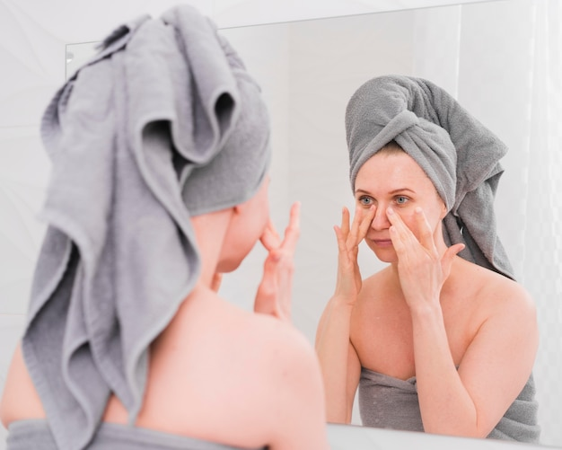 Woman wearing towels looking at herself in the mirror