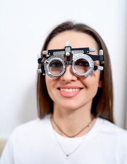 視力矯正用トライアルセットを着用した女性。クリニックで視力をテストします。眼科の概念。