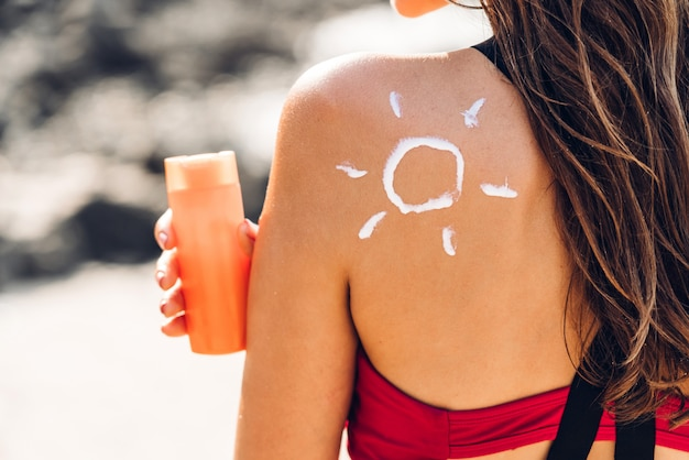 Woman wearing two piece bikini applying suncream with sun drawn on back on the tropical beach. summer vacations