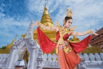 Woman wearing typical thai dress on old temple background