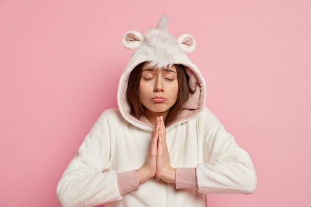 Женщина, носящая пижаму единорога