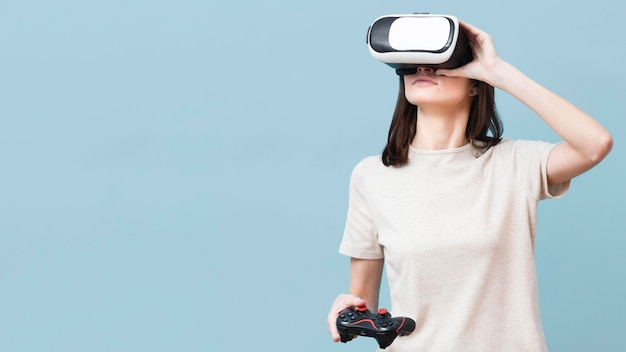 Woman wearing virtual reality headset and holding remote control