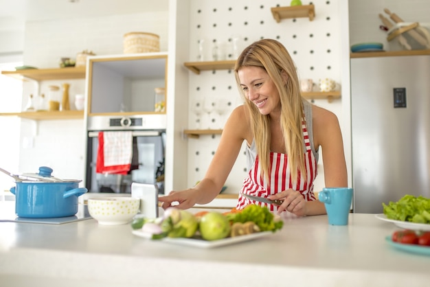 Woman wearing a white apron with red lines looking at her device and cooking something
