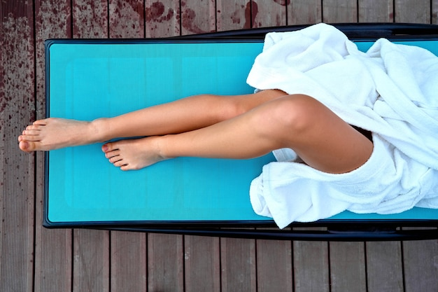 Woman wearing white bathrobe with beautiful smooth slim long legs lying on a lounger at spa resort