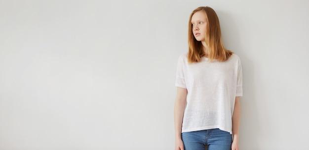 立っている白い空白のtシャツを着ている女性