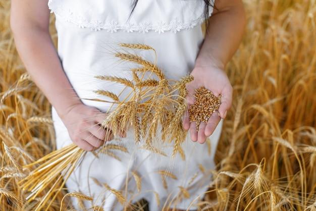 Женщина в белом платье держит колосья пшеницы в одной руке и зерна пшеницы в другой.