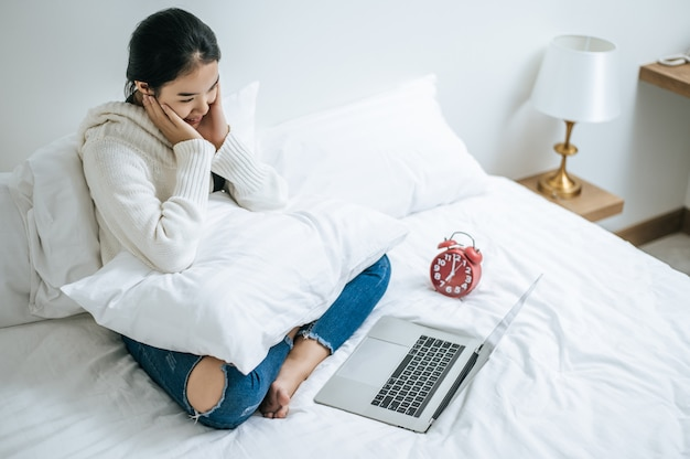 A woman wearing a white shirt on the bed and playing laptop happily.