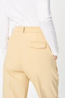 Donna che indossa una camicia bianca e un modello di pantaloni beige