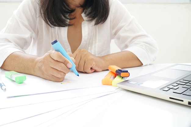 A woman wearing a white shirt checking documents
