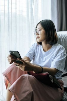 A woman wearing a white shirt, sitting on the bed and playing a smartphone.